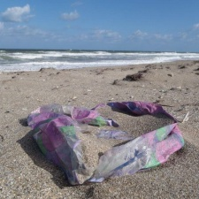 Mylar balloon partially covered in beach sand
