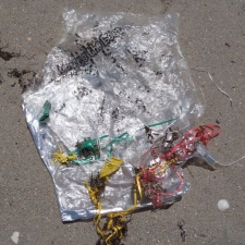 Plastic bag, bits of latex balloons and ribbon littering beach