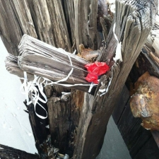latex balloon and river caught on pier wood beam