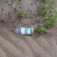 plastic sports drink bottle, covered in the wind blown sand in the dunes