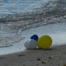 5 latex balloons on ocean water edge