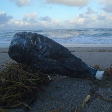 oil-laden plastic bottle trashed on beach