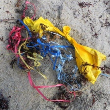 balloons and ribbons littering beach