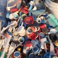 Pile of plastic caps and combs from beach cleanup