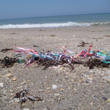 balloon ribbons and latex burst balloon littering beach