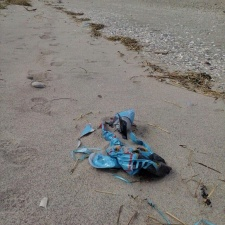 mylar balloon trash and ribbon polluting beach