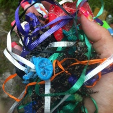 pile of latex balloons and ribbons polluting beach